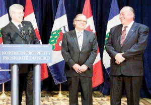 From left, Prime Minister Stephen Harper, AANDC Minister Bernard Valcourt and NWT Premier Bob McLeod answer questions on the devolution deal signed in Yellowknife on Mar. 11. (Photo by GNWT Executive)