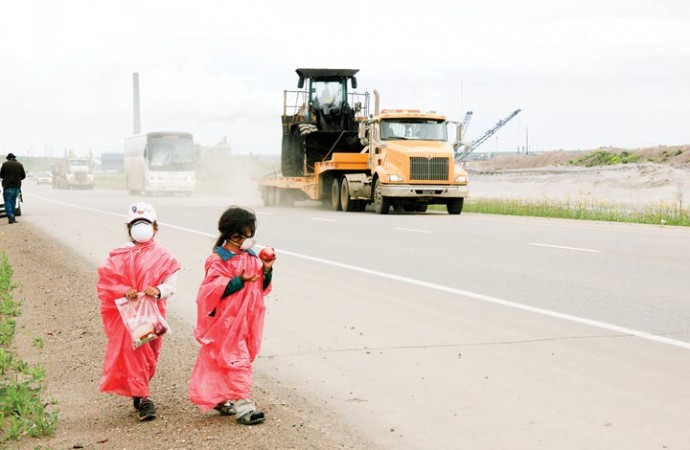 A constant stream of traffic from Syncrude's oilsands facilities blasts by as young marchers try to mask themselves from the pollution.