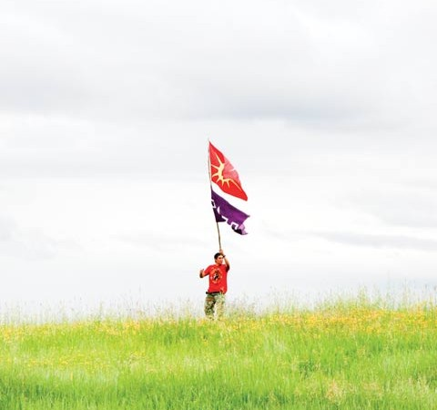 Chris Hill from Six Nations flies his Mohawk flags near one of Syncrude's tailings ponds.
