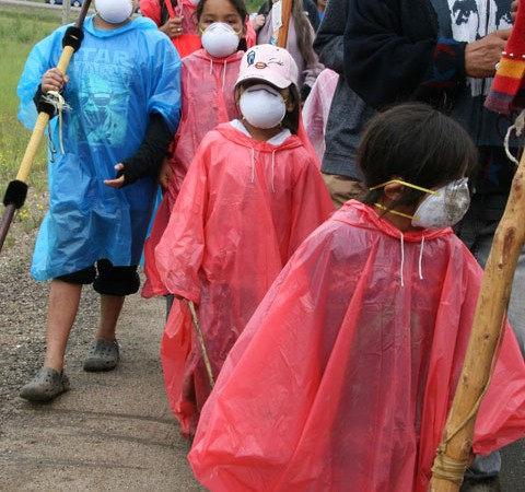 Masked children join the 14-km walk around Syncrude's oilsands facilities.