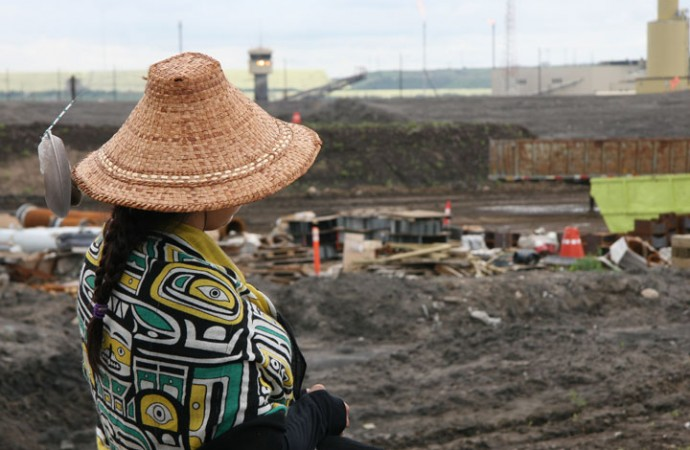 A walker from the West Coast looks on at Syncrude's oilsands facility.