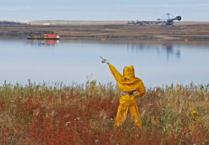 A scarecrow meant to deter water fowl stands guard over an oilsands tailing pond.