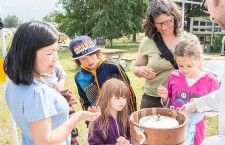 Min Sun, left, and the Desrochers family from Gatineau, Que. get a lesson in making ice cream the old-fashioned way on Saturday at Mission Park in Fort Smith during National Parks Day, where Northern Life Museum staff also taught the art of candle-making to visitors.