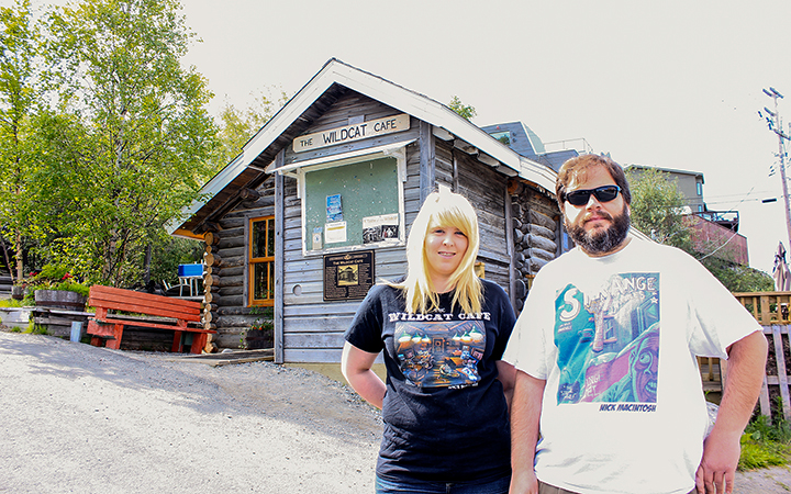 Paulina Lambert wears one of only three t-shirts created by Nick MacIntosh, right, sold before Yellowknife city officials warned the Yellowknife artist that he had used their trademark without permission and demanded that he turn his remaining stock over to them.