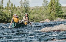 Hall, right, and one of his adventurers navigate through a water channel en route to their next campsite.