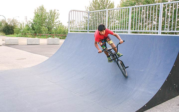 Noah Lafleur, 11, rides his bike around the half pipe at Hay River's newly-opened skatepark on Sunday evening.