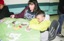Mother and son Rhonda Marcel and Landon Thacker make masks at one of the Helping Hands to Success after school art programs, hosted at the Athabasca Delta Community School.