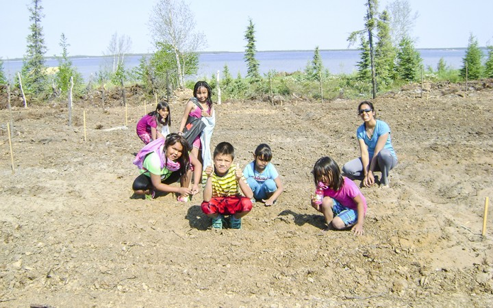Children plant seeds at the first-ever community garden in Gameti. At over 2,000 square metres, the plot is the largest community garden in the Northwest Territories.