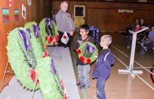 Joshua Norman and Arthur Benoit-Cardinal place a wreath on behalf of the Junior Kindergarten to Grade 3 classes.