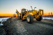 A grader smooths a top layer of gravel along the Inuvik to Tuktoyaktuk highway. At any given time, as many as 100 vehicles, from rock haulers to excavators to water trucks, are working away on the $299-million project.