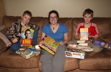 Finn Johnson, left, his mom Kirsten Bradley and brother Olie Johnson pull out their favourite books and games for national Family Literacy Day, taking place on Jan. 27.