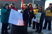 Public Service Alliance of Canada president Robyn Benson throws an open letter from Hay River Mayor Andrew Cassidy into a burning barrel. The letter to striking employees issued Wednesday asks them to cross the picket line and get back to work.  (Photo: Michael Aubry)