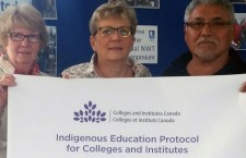 Aurora College board of directors chair Sydney O'Sullivan, left, president Jane Arychuk and Elder representative Paul Andrew hold the protocol that will be displayed at all three campuses.
